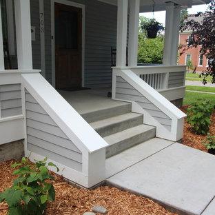 Ispirazione per un portico classico di medie dimensioni e davanti casa con pavimentazioni in cemento e un tetto a sbalzo