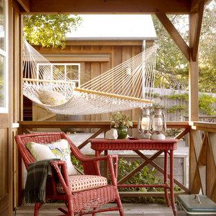 Exempel på en rustik veranda framför huset, med trädäck och takförlängning