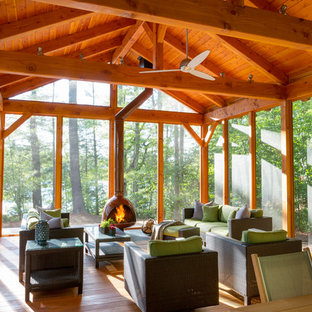 This is an example of a rustic screened-in back porch design in Boston.