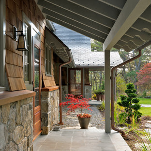 This is an example of a mid-sized craftsman concrete paver porch design in Boston with a roof extension.