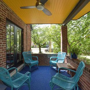 Esempio di un piccolo patio o portico con pannellatura nel cortile laterale con lastre di cemento e un tetto a sbalzo