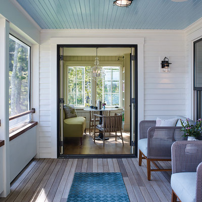 Beach style screened-in porch idea in Portland Maine with decking and a roof extension