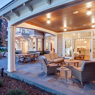 This is an example of a traditional backyard screened-in verandah in Minneapolis with natural stone pavers and a roof extension.