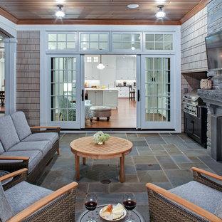 Aménagement d'un porche arrière classique avec des pavés en pierre naturelle, une extension de toiture et un foyer extérieur.