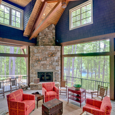 Inspiration for a large rustic stone side porch remodel in Other with a fire pit and a roof extension