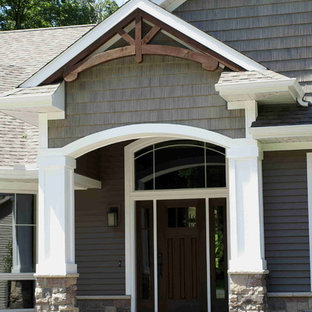 Inspiration for a mid-sized craftsman concrete front porch remodel in Other with a roof extension
