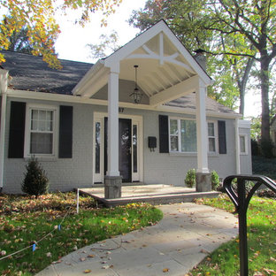 Small classic stone front porch idea in DC Metro with a roof extension