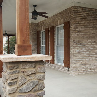 Large arts and crafts concrete front porch idea in Charlotte with a roof extension