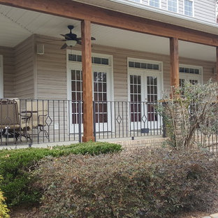 This is an example of a large craftsman concrete front porch design in Charlotte with a roof extension.
