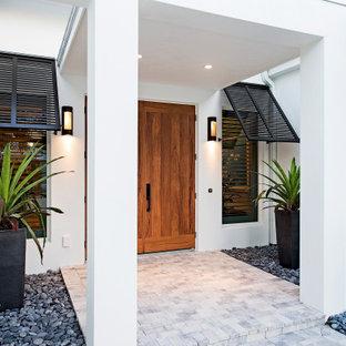 Immagine di un portico tropicale di medie dimensioni e davanti casa con pavimentazioni in mattoni e un tetto a sbalzo