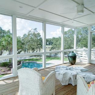 Ejemplo de porche cerrado costero, de tamaño medio, en patio trasero y anexo de casas, con entablado