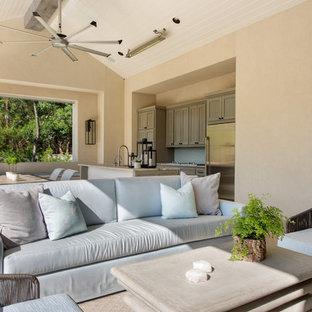 Foto di un grande patio o portico mediterraneo dietro casa con un tetto a sbalzo e piastrelle