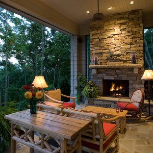 На фото: веранды в стиле рустика с местом для костра и покрытием из каменной брусчатки