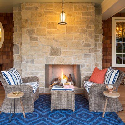 Large beach style front porch photo in Minneapolis with a fire pit and a roof extension