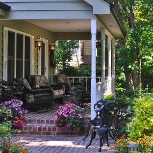 Diseño de terraza tradicional, de tamaño medio, en patio delantero, con jardín de macetas y adoquines de ladrillo