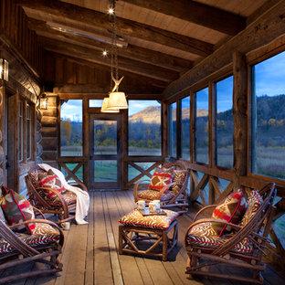 На фото: веранда среднего размера на заднем дворе в стиле рустика с крыльцом с защитной сеткой, настилом и навесом с