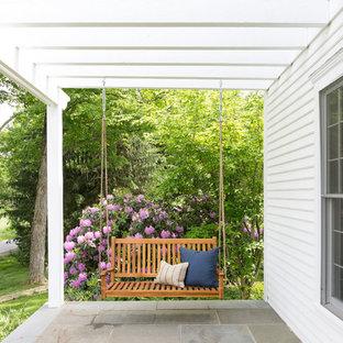Foto di un portico country davanti casa con pavimentazioni in cemento e una pergola