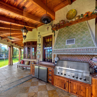 Tuscan outdoor kitchen porch photo in Miami with decking and a roof extension
