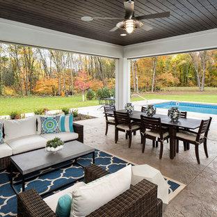 Ejemplo de porche cerrado clásico renovado, extra grande, en anexo de casas, con suelo de hormigón estampado