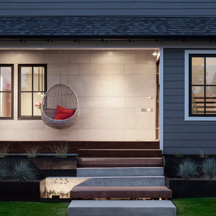 This is an example of a mid-sized contemporary concrete front porch design in Salt Lake City with a roof extension.
