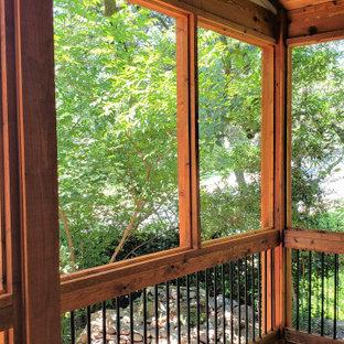 Idee per un portico rustico dietro casa con un tetto a sbalzo e parapetto in materiali misti