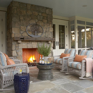 Large elegant stone side porch photo in New York with a fire pit and a roof extension
