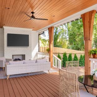 Immagine di un grande portico stile marinaro dietro casa con un caminetto e un tetto a sbalzo