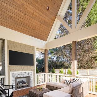 Esempio di un grande portico tradizionale dietro casa con un caminetto e un tetto a sbalzo