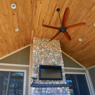Arts and crafts tile back porch idea in Indianapolis with a roof extension
