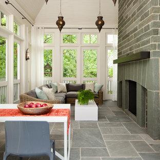 Immagine di un portico stile marino dietro casa e di medie dimensioni con un portico chiuso, pavimentazioni in pietra naturale e un tetto a sbalzo