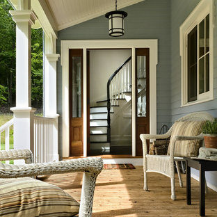 Elegant porch photo in New York with decking and a roof extension