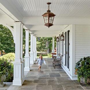 Immagine di un portico country con pavimentazioni in pietra naturale e un tetto a sbalzo
