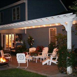 Large trendy back porch idea in Other with a pergola
