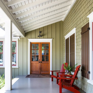 Coastal concrete front porch photo in Jacksonville with a roof extension