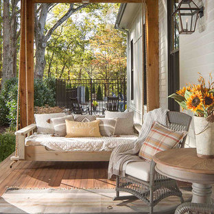 This is an example of a country side porch design in Atlanta with decking and a roof extension.