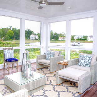 This is an example of a large beach style screened-in back porch design in New York with decking and a roof extension.