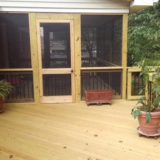 Idee per un grande portico dietro casa con un portico chiuso e parapetto in materiali misti