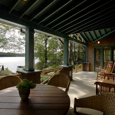 Large mountain style front porch photo in New York with a roof extension