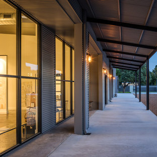 This is an example of a large industrial concrete front porch design in Houston with a roof extension.
