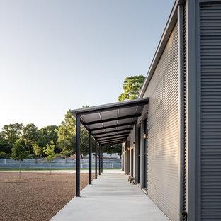 Idee per un grande portico industriale davanti casa con lastre di cemento e un parasole