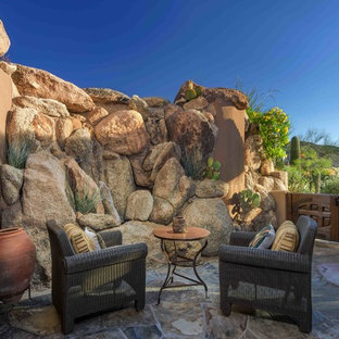 This is an example of a small southwestern stone side porch design in Phoenix.
