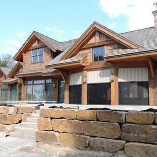 Huge mountain style stone screened-in back porch photo in Minneapolis with a roof extension
