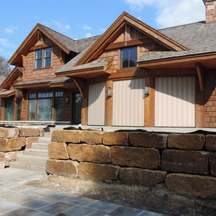 Inspiration for a huge rustic stone screened-in back porch remodel in Minneapolis with a roof extension