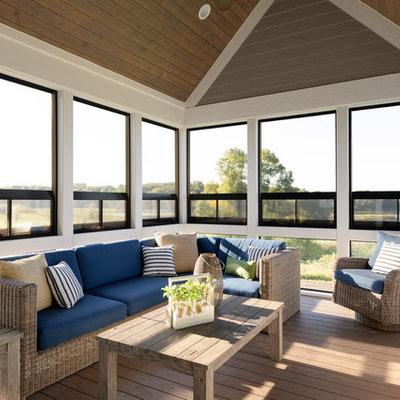 Beach style screened-in back porch idea in Minneapolis with a roof extension and decking