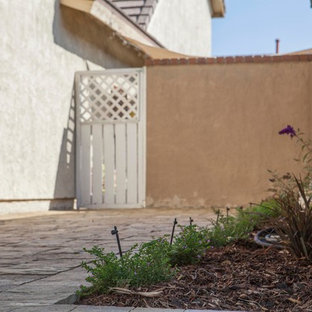 Mid-sized tuscan stone side porch photo in Orange County