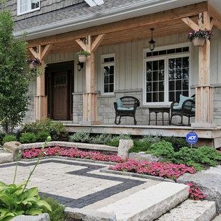 Idee per un portico american style di medie dimensioni e davanti casa con pavimentazioni in pietra naturale e un tetto a sbalzo