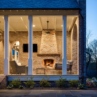 Large classic back porch idea in New Orleans with a fireplace and a roof extension