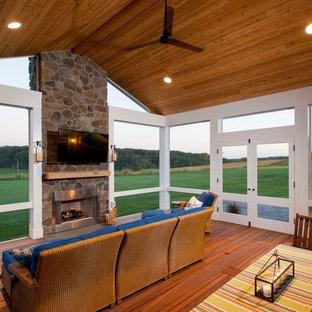 Idéer för att renovera en stor rustik innätad veranda på baksidan av huset, med trädäck och takförlängning