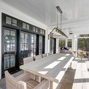 Ispirazione per un grande portico country dietro casa con un portico chiuso, piastrelle e un tetto a sbalzo