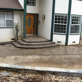Mid-sized mountain style concrete paver front porch idea in Other